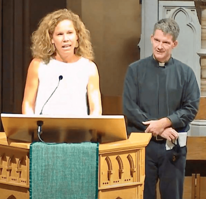 Katie Jansen Larson makes an announcement at St. Francis Xavier College Church, as Pastor Dan White, SJ, looks on.
